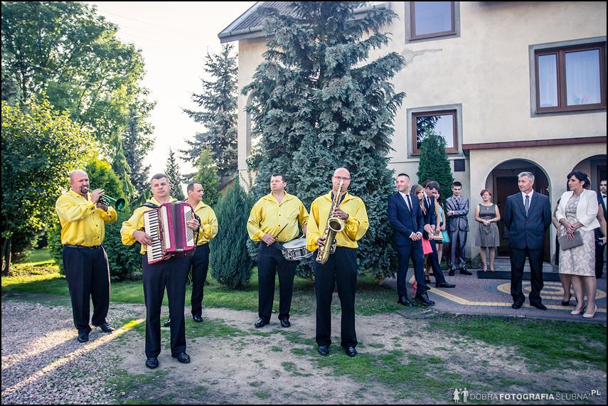 orkiestra gra przed domem panny młodej