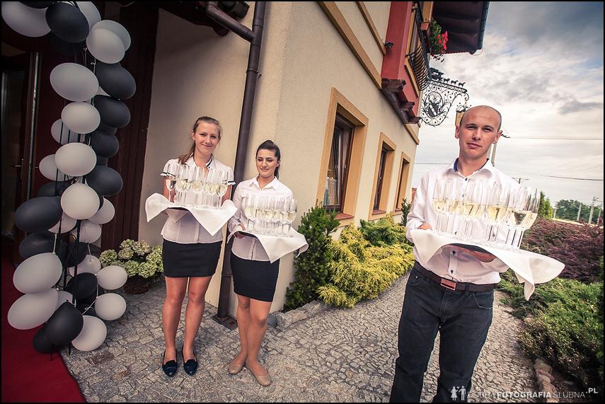 kelnerzy z szampanem przed salą weselną
