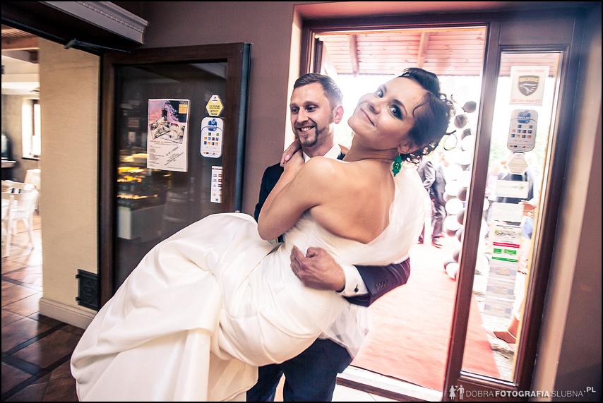 młody wnosi młodą na rękach na salę weselną