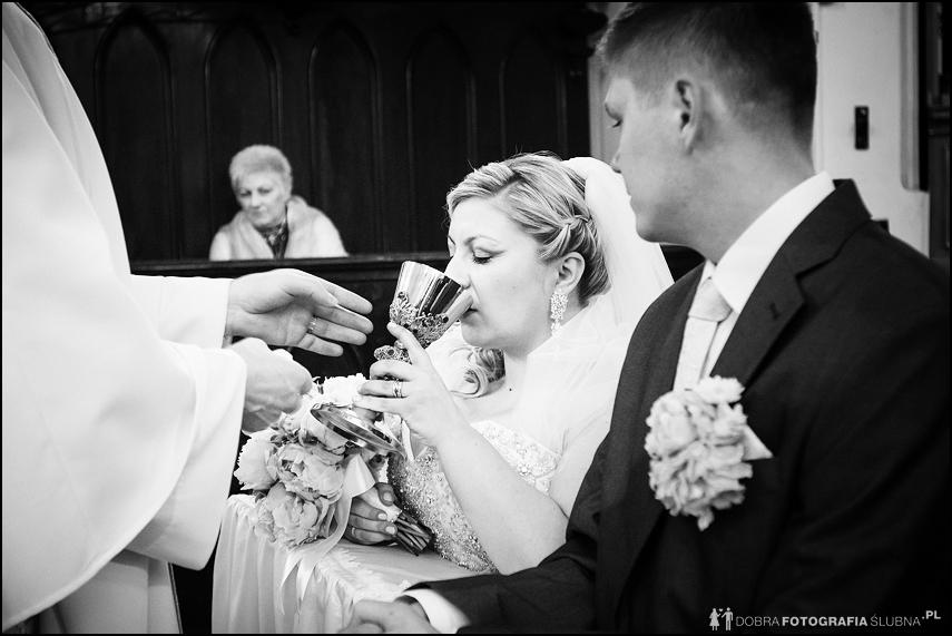 czarnobiałe zdjęcia ślubne- panna młoda pije wino