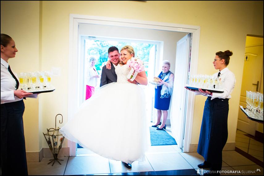 mąż wnosi na rękach pannę młodą na salę weselną